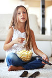 Child watching tv. 8 years old child watching tv sitting on a white carpet at home alone Stock Photo