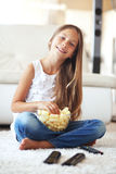 Child watching tv. 8 years old child watching tv sitting on a white carpet at home alone Royalty Free Stock Photography