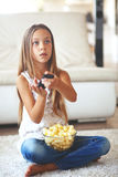 Child watching tv. 8 years old child watching tv sitting on a white carpet at home alone Royalty Free Stock Image