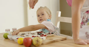 Child watching woman sprinkle candy on muffins Royalty Free Stock Photo