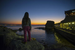 Child watcing acre port at sunset Royalty Free Stock Image