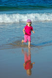 Child, water and fun. Little happy blond caucasian girl child in pink clothes playing in the sea and running in the water on the beach having great holiday fun Royalty Free Stock Photo