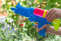 Child with a water pistol outdoors Stock Photos