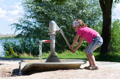 Child at the water pump. Little girl playing in the summer at a water pump royalty free stock photo