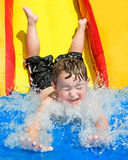 Child on water slide. Young child has fun splashing into pool after going down water slide during summer Royalty Free Stock Photos