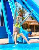 Child on water slide at aquapark. Summer holiday stock image