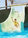 Child on water slide at aquapark. Summer holiday royalty free stock image