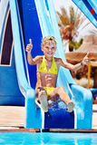 Child on water slide at aquapark. Summer holiday royalty free stock photography