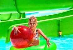 Child on water slide at aquapark. Beach ball stock photo