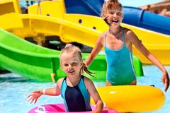 Child on water slide at aquapark. Blue bikini stock photography