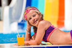 Child on water slide at aquapark drinking cold squeezed orange juice. Royalty Free Stock Photos