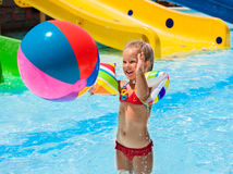 Child on water slide at aquapark. Girl playing beach ball. Summer holiday stock image
