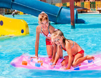 Child on water slide at aquapark. Inflatable beach mattress royalty free stock photography