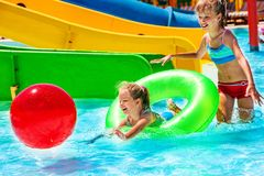 Child on water slide at aquapark. Playing with beach ball on summer holiday royalty free stock image