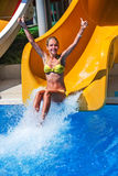 Child on water slide at aquapark show thumb up. Royalty Free Stock Photo