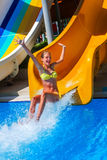 Child on water slide at aquapark show thumb up. Stock Image