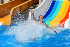 Child on water slide at aquapark show thumb up. Happy kid on water slide at water park hands up. There are some water slides with flowing splash water in aqua royalty free stock image