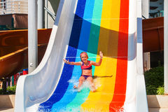 Child on water slide at aquapark show thumb up. Child little girl on water slide at aquapark show hands up. There are some water slides with flowing water in Stock Image