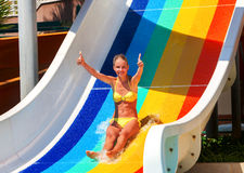 Child on water slide at aquapark show thumb up. Royalty Free Stock Photos