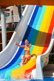 Child on water slide at aquapark show thumb up. Stock Images