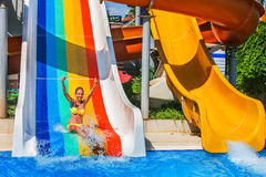 Child on water slide at aquapark show thumb up. There are some water slides with flowing water in aqua park. Summer water park holiday. Outdoor Royalty Free Stock Image