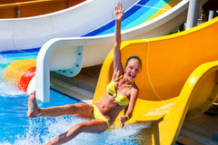 Child on water slide at aquapark show thumb up. Royalty Free Stock Image