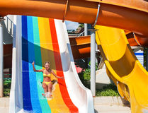 Child on water slide at aquapark show thumb up. There are some water slides with flowing water in aqua park. Summer water park holiday. Outdoor royalty free stock images