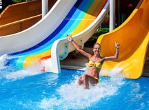 Child on water slide at aquapark show thumb up. There are some water slides with flowing water in aqua park. Summer water park holiday. Outdoor. Summer freedom Royalty Free Stock Photo