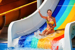 Child on water slide at aquapark show thumb up. Wet child on water slide at aquapark shows thumb up on water slides with flowing water in water park. Summer stock image