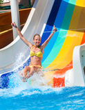 Child on water slide at aquapark shows thumb up. Child on water slide at aquapark shows thumb up two hands . There are some water slides with flowing water in stock photography
