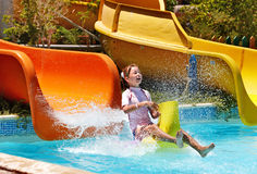 Child on water slide at aquapark. Stock Photo