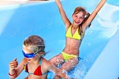 Child on water slide at aquapark. Royalty Free Stock Photo