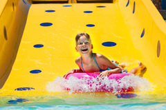 Child on water slide at aquapark. Summer holiday stock images