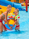 Child on water slide at aquapark. Summer holiday. Beach ball stock photography