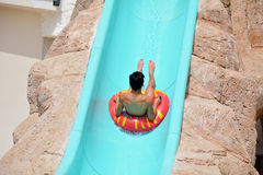 Child on water slide at aquapark. Summer holiday Royalty Free Stock Image