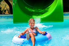 Child on water slide at aquapark. Summer holiday. Green and blue royalty free stock image