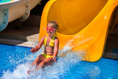 Child on water slide in aquapark. Child on water slide at aquapark. Two water slides with flowing water in aqua park. Touch point of water. Summer holiday royalty free stock photo