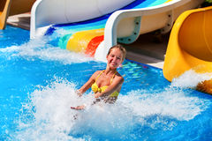 Child on water slide at aquapark water splashes. Stock Images