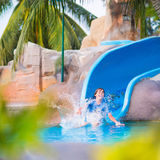 Child on water slide. Happy boy on water slide in a swimming pool having fun during summer vacation in a beautiful tropical resort Stock Image