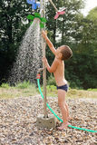 Child in water under garden shower Stock Photography