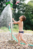 Child in water under garden shower Royalty Free Stock Images