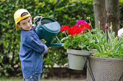 Child with watering can. Child watering flowers with watering can Stock Photo