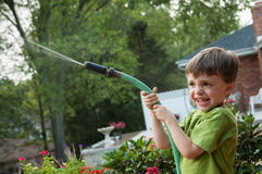 Child Watering Garden with Hose Royalty Free Stock Photo