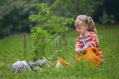 Child with orange water can outside watering just planted tree