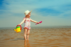 Child with watering-pot on the seashore Royalty Free Stock Photos