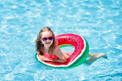 Child in swimming pool. Kids swim. Water play. Child with watermelon inflatable ring in swimming pool. Little girl learning to swim in outdoor pool of tropical royalty free stock photo