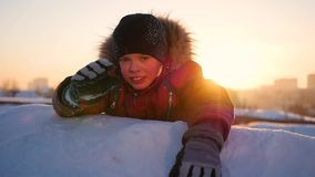 A child waves the hand in winter Park, in the background of the sunset. snow winter landscape. Sunset time stock video footage
