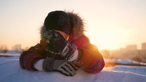A child waves the hand in winter Park, in the background of the sunset. snow winter landscape. Sunset time stock video