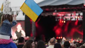 Child waving of flag Ukraine, little girl at concert, patriotic upbringing kid, concert crowd on rock festival, stock video
