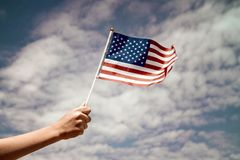 Child waving US flag. On the sky background royalty free stock photos